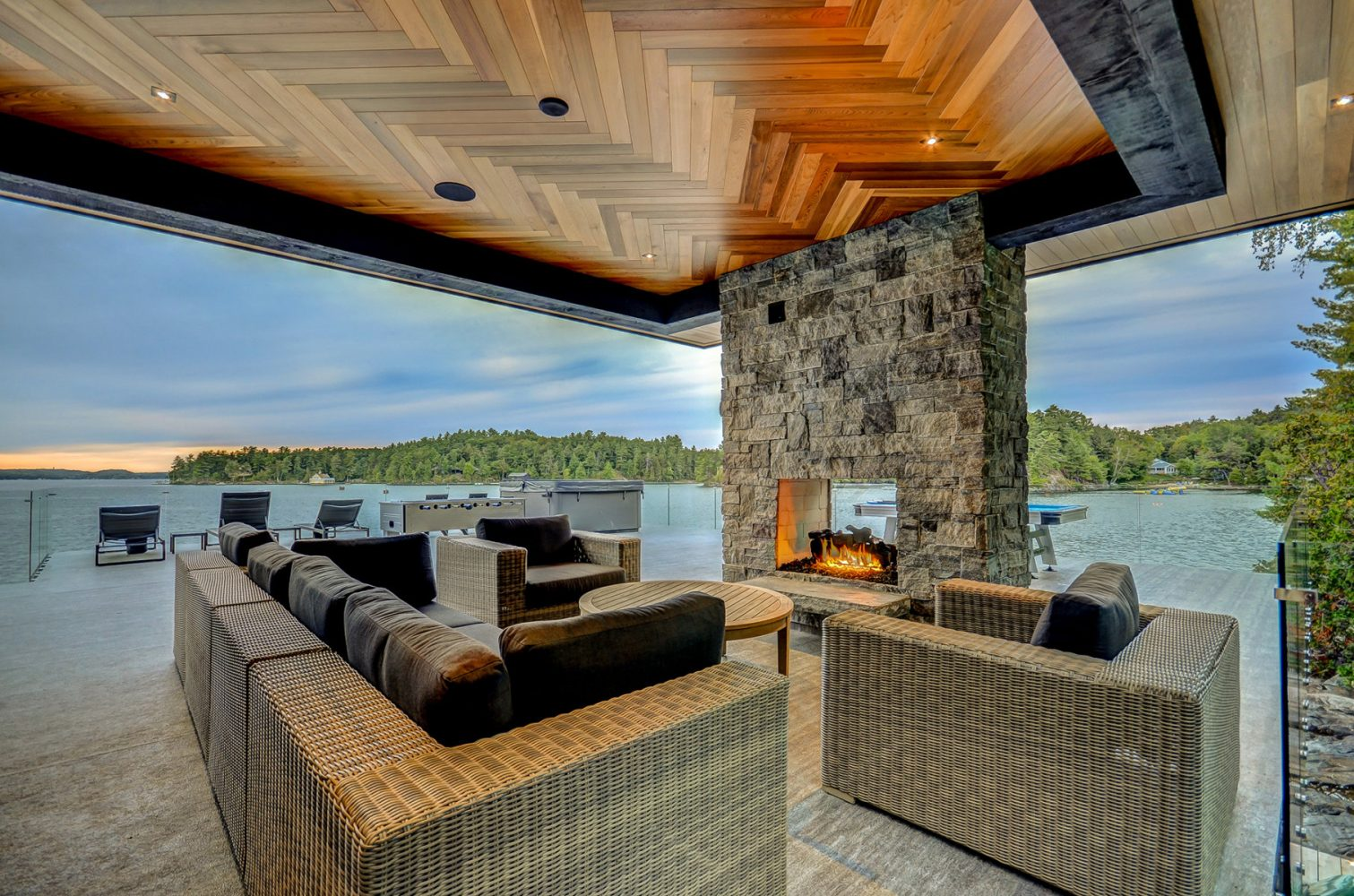 Double sided fireplace in the top lounge of a luxury boathouse in Muskoka