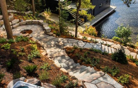 Luxury Muskoka Landscaping by PattyMac with stone fire pit, walkway and boathouse