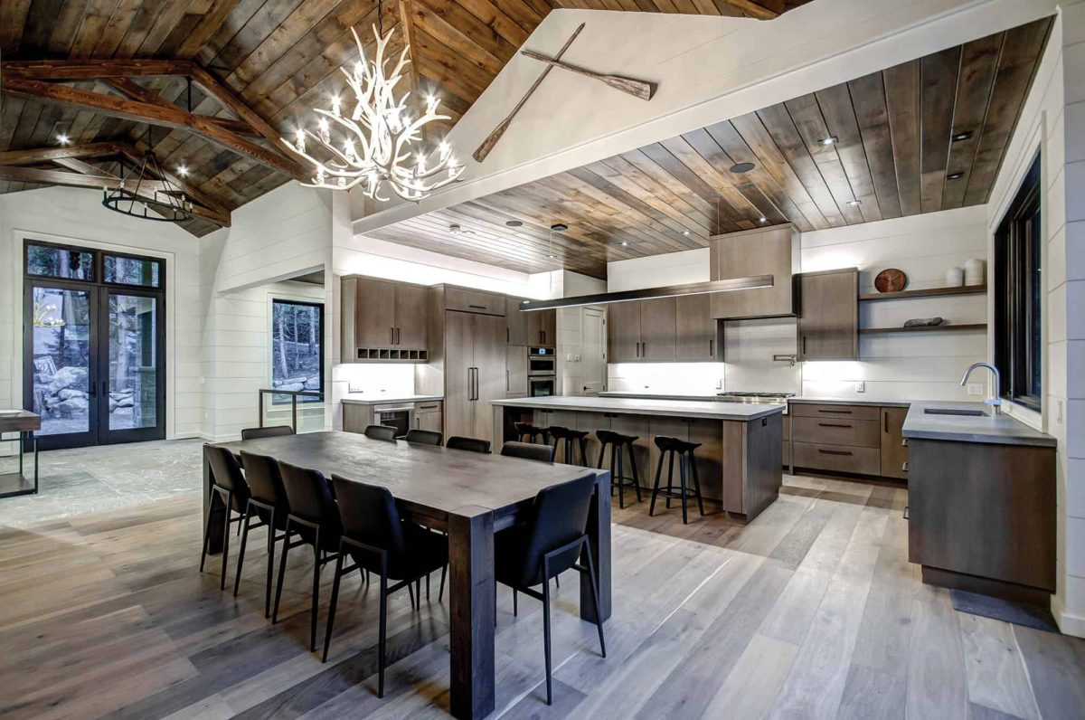 Contemporary open kitchen mixed with traditional timber trusses in Muskoka by PattyMac
