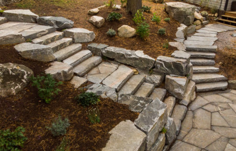 Stone steps with retaining walls down to a stone patio by PattyMac