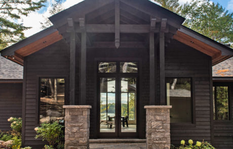 Grand entrance for a Muskoka Cottage by PattyMac with black wood siding