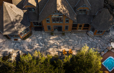 Stone patio and lounge space with landscaping at Muskoka cottage by PattyMac
