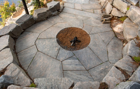 Stone fire pit with retaining walls by PattyMac for luxury Muskoka cottage