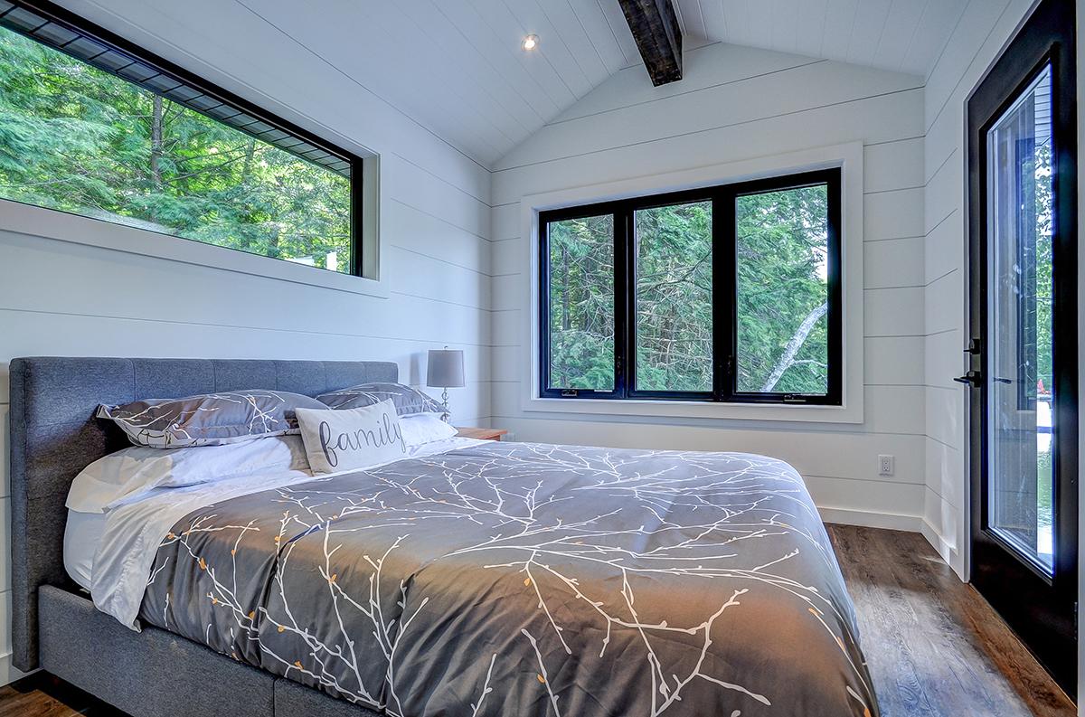 Master bedroom fo a cozy Muskoka boathouse built by PattyMac