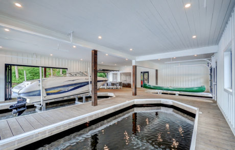 Contemporary boathouse with 3 slips and a lounge area for a Muskoka boathouse by PattyMac