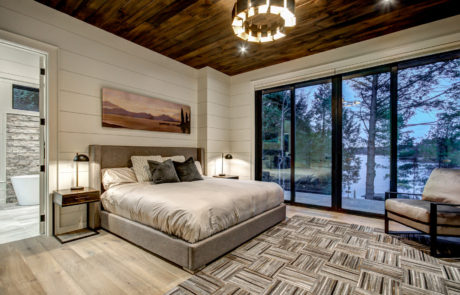 Contemporary master bedroom with beautiful views and private balcony of Muskoka cottage