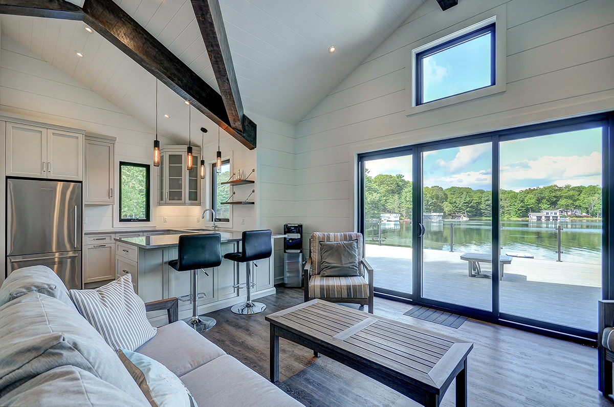 Contemporary shiplap cladded boathouse with kitchenette and timber trusses by PattyMac