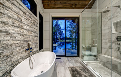 Steam shower and standalone tub with rock accent wall in a 4 piece bathroom in a luxury Muskoka cottage