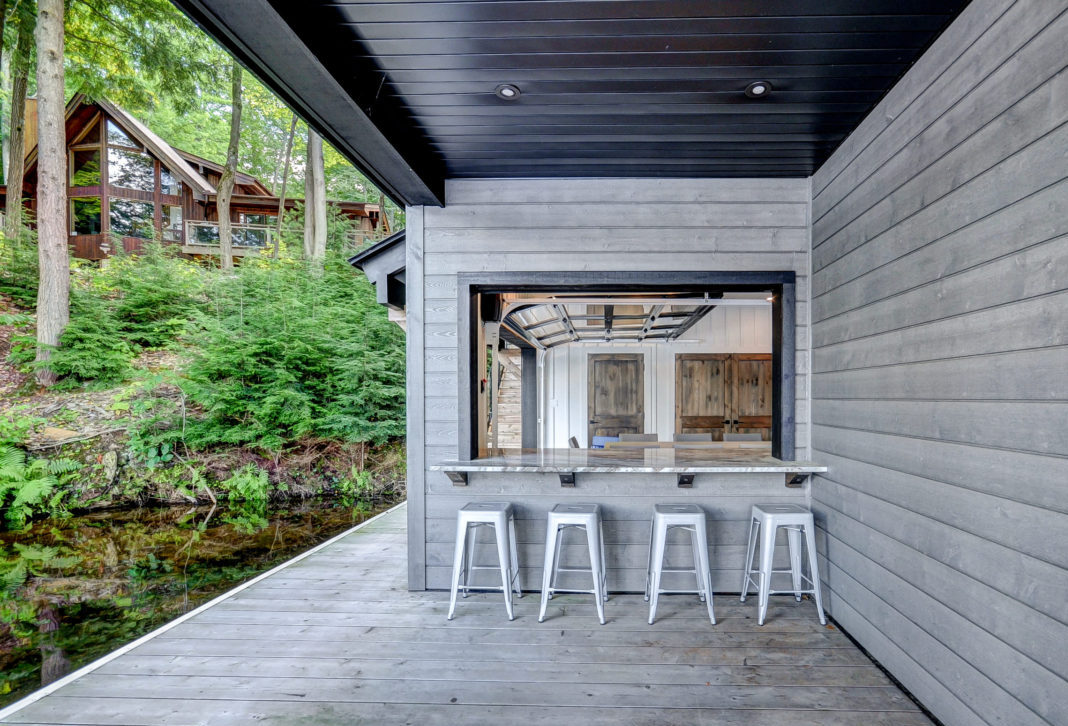 Covered walk-up bar and lounge area at a Muskoka boathouse by PattyMac