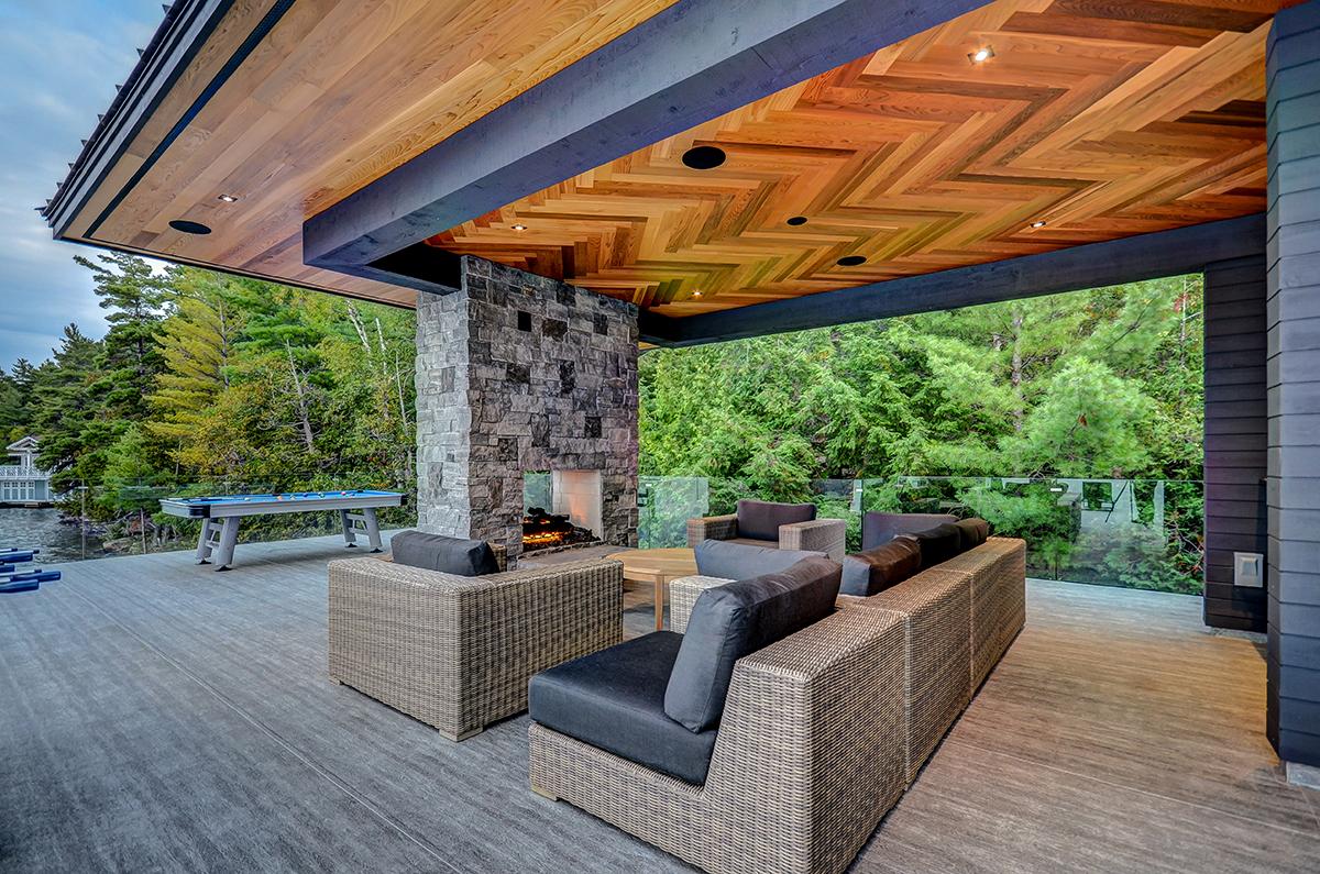 Double sided fireplace with luxury lounge on second floor of Muskoka boathouse