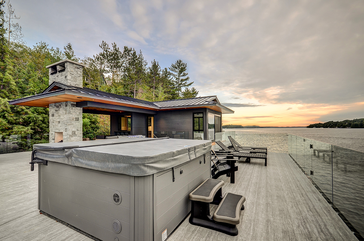 Glass railing are prevalent throughout this Muskoka boathouse giving great views of the lake