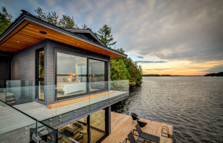 Contemporary boathouse in Muskoka with glass railing