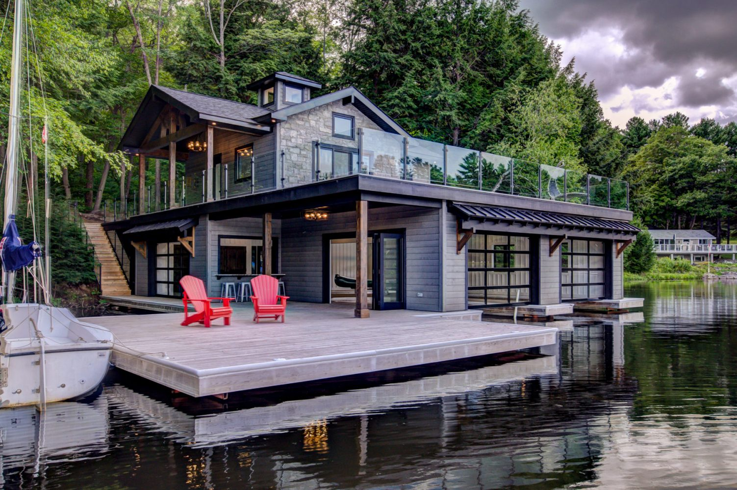 3 slip boathouse with living quarters above and glass railings built by PattyMac