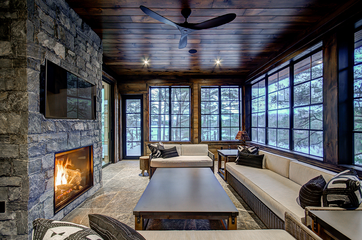 Muskoka room with double sided fireplace and stone floors