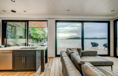 Contemporary lake-level boathouse with oversized windows and beautiful views by PattyMac