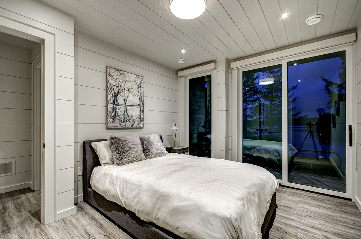 Bedroom with shiplap panelling and private balcony in luxury Muskoka cottage