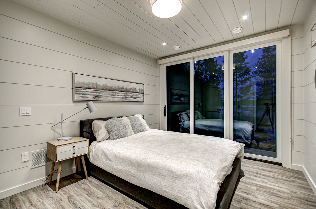 Luxury Muskoka cottage bedroom with private balcony and white shiplap by PattyMac