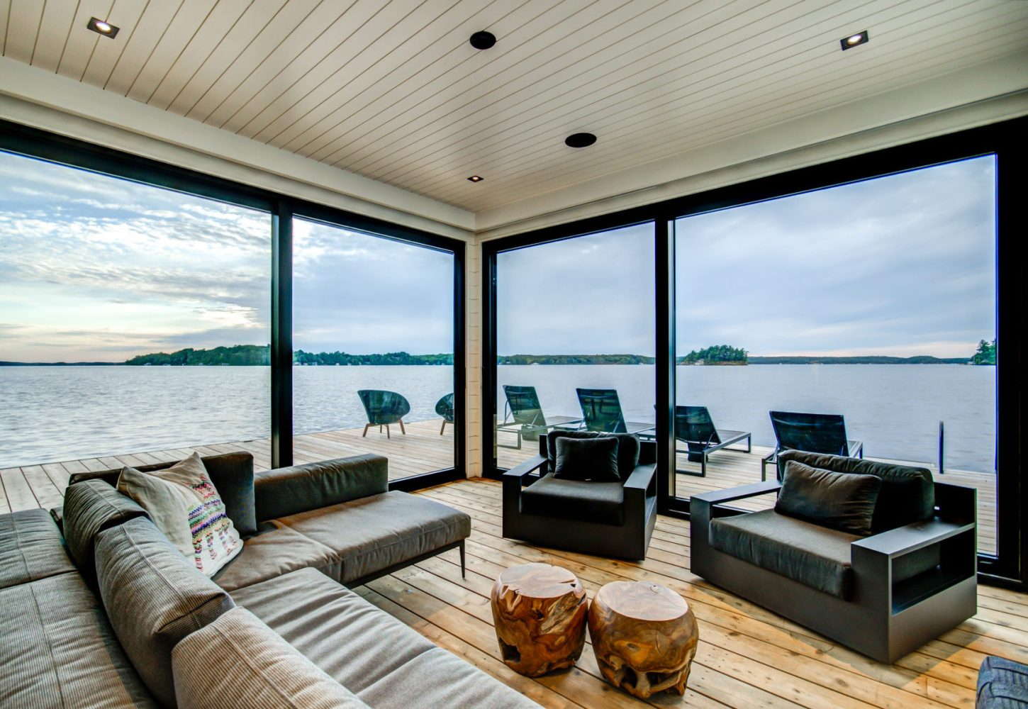 Contemporary modern lounge at lake level boathouse by PattyMac
