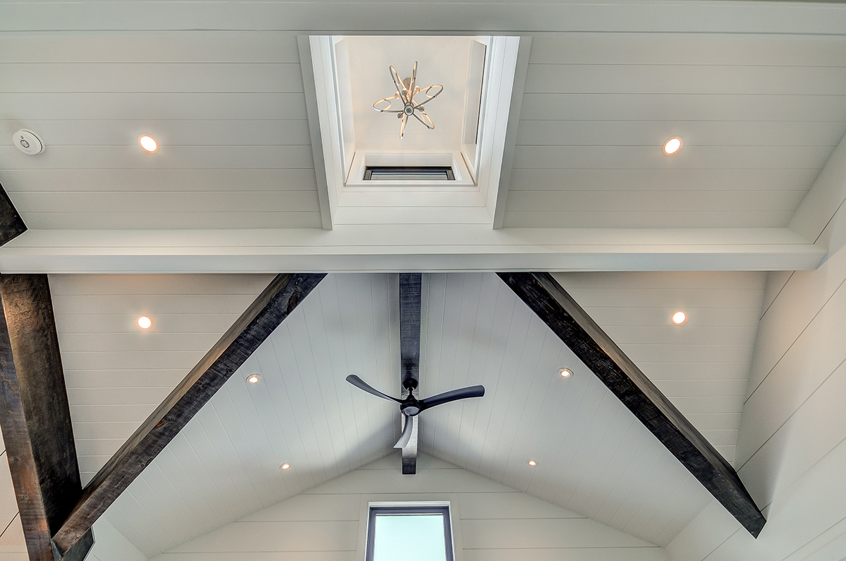 Custom timber truss accents with interior shiplap in a Muskoka boathouse by PattyMac
