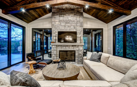 Double sided fire place and timber trusses in luxury Muskoka cottage by PattyMac