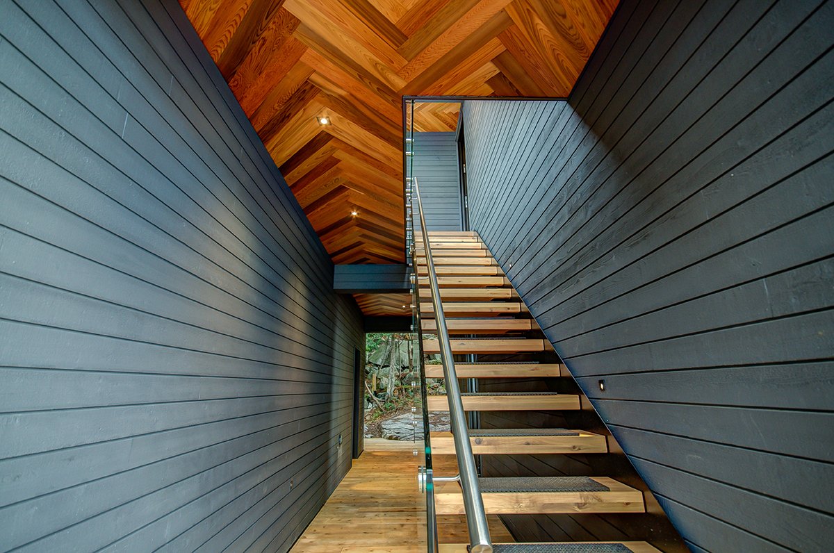 Contemporary open staircase to second floor of a Muskoka boathouse with black wood siding by PattyMac