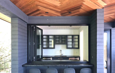 Accordion window bar at a second level luxury lounge area of a Muskoka boathouse
