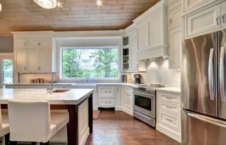 All white traditional kitchen with recessed shaker style cabinets and stone backsplash