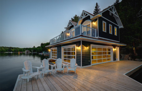 2 level boathouse in Muskoka at dusk with Muskoka Chairs