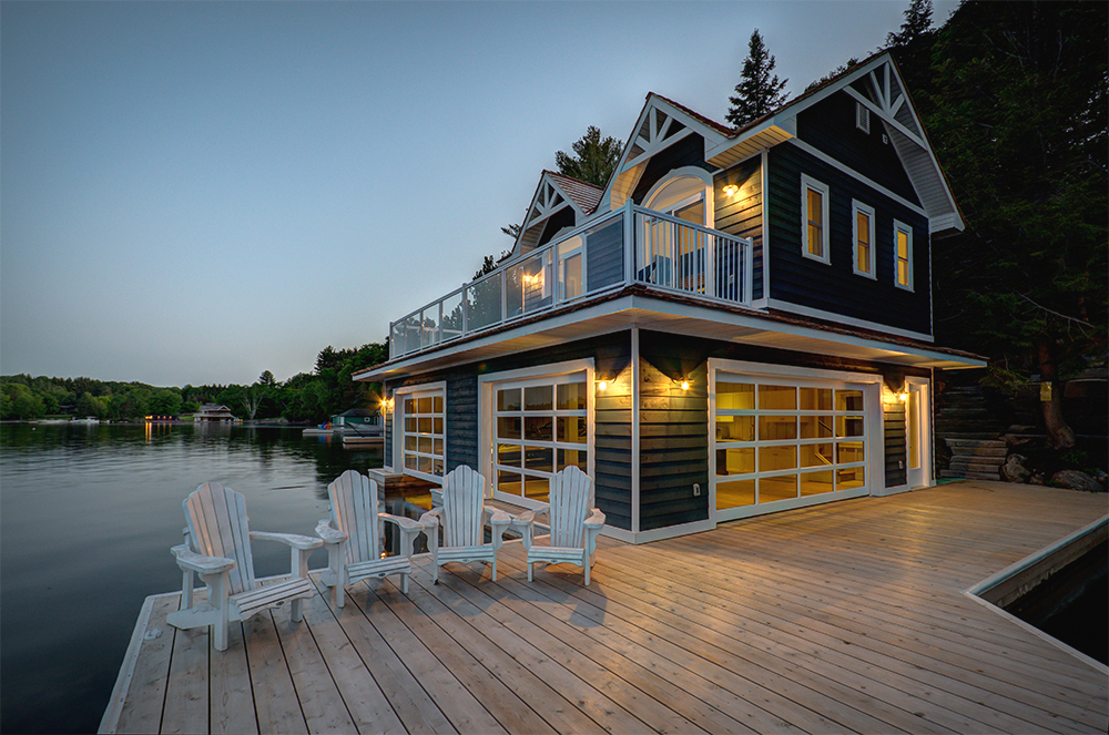 2 level boathouse in Muskoka at dusk with Muskoka Chairs